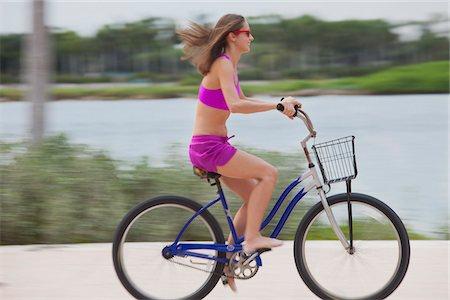Girl cycling barefoot Stock Photo - Premium Royalty-Free, Code: 653-05975961