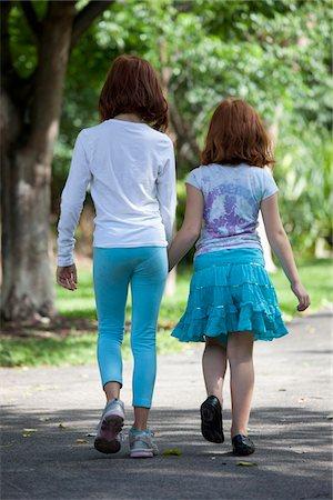 preteen touch - Girls walking through park hand in hand Stock Photo - Premium Royalty-Free, Code: 653-05975989