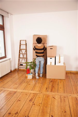A woman pushing a moving box into place on top of a stack of boxes Stock Photo - Premium Royalty-Free, Code: 653-05976078