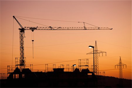 A construction crane and electricity pylons silhouetted against a sunset sky Stock Photo - Premium Royalty-Free, Code: 653-05976173