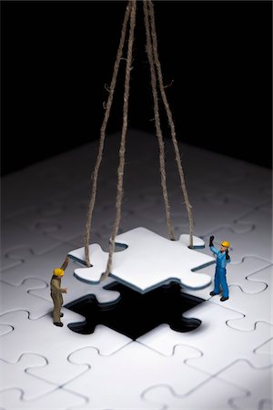 Miniature workmen guiding a hanging puzzle piece into place Stock Photo - Premium Royalty-Free, Code: 653-05976187