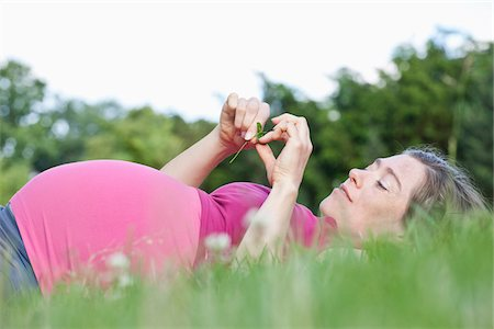 pregnant low angle - A pregnant woman lying in the grass, side view Stock Photo - Premium Royalty-Free, Code: 653-05976342