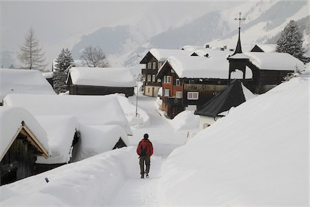 Man strolling through snow covered village Stock Photo - Premium Royalty-Free, Code: 653-05976438