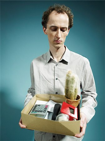 A man carrying a box of possessions after being fired Stock Photo - Premium Royalty-Free, Code: 653-05976483