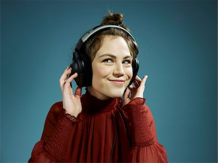 A young hip woman wearing headphones and smiling Stock Photo - Premium Royalty-Free, Code: 653-05976524