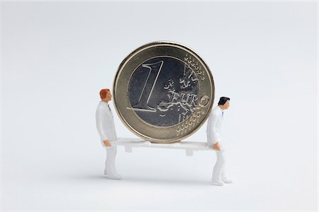 Miniature paramedic figurines carrying a euro coin on a stretcher Stock Photo - Premium Royalty-Free, Code: 653-05976578