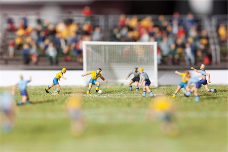 Miniature figurines of two soccer teams playing a soccer match Stock Photo - Premium Royalty-Free, Code: 653-05976597