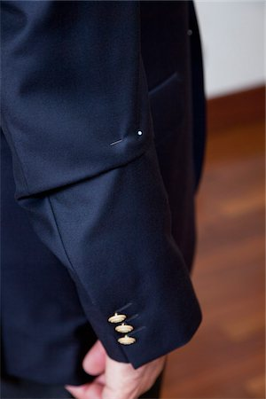Detail of a pin in the sleeve of a man's suit jacket Stock Photo - Premium Royalty-Free, Code: 653-05976672