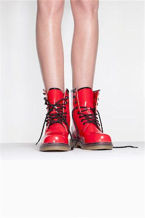 focus on background - A woman wearing red patent leather boots, low section Stock Photo - Premium Royalty-Free, Code: 653-05976734