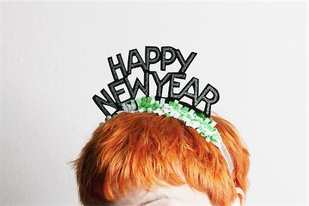 A woman wearing a party tiara with Happy New Year on it, top of head Stock Photo - Premium Royalty-Free, Code: 653-05976746