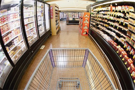 A shopping cart on an aisle in a supermarket, personal perspective Stock Photo - Premium Royalty-Free, Code: 653-05976758