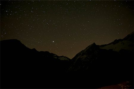 star sky night - A starry sky behind silhouetted mountains Stock Photo - Premium Royalty-Free, Code: 653-05976774