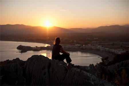 A silhouetted person sitting atop a hill watching the sunset, Rhodes, Greece Stock Photo - Premium Royalty-Free, Code: 653-05976771