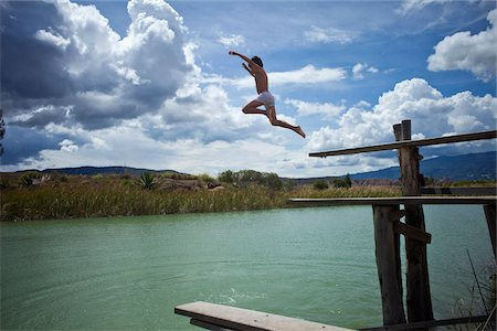 A young boy jumping into a lake Stock Photo - Premium Royalty-Free, Code: 653-05976787