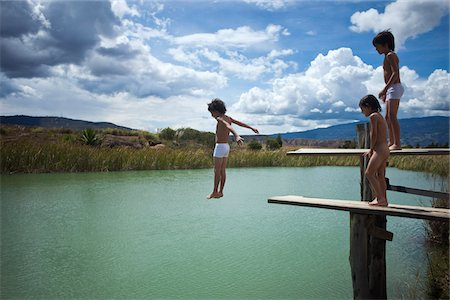 A boy jumping into water while his twin brother and friend watch Stock Photo - Premium Royalty-Free, Code: 653-05976798