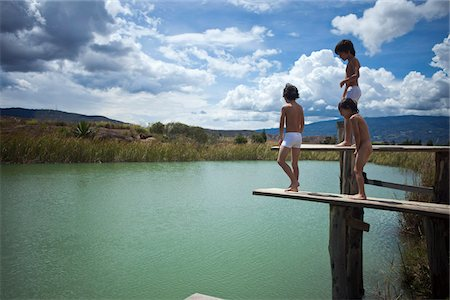 Twin brothers and their friend preparing to jump into a lake Stock Photo - Premium Royalty-Free, Code: 653-05976791