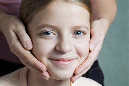 preteen touch - Portrait of daughter with Mother's hands on her cheeks Stock Photo - Premium Royalty-Free, Code: 653-05976870