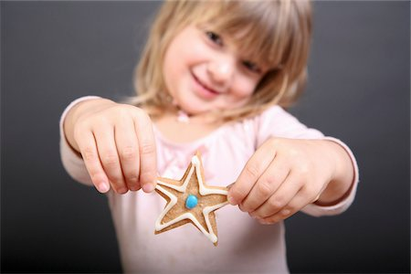 shape - A girl holding out up a star shaped Christmas cookie Stock Photo - Premium Royalty-Free, Code: 653-05976889