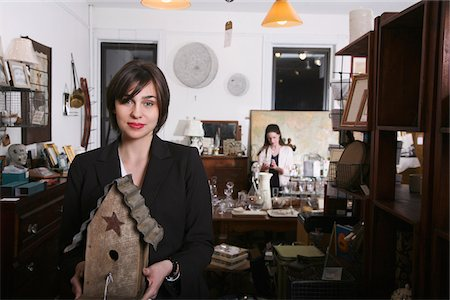 A woman holding an old birdhouse in an antiques shop Stock Photo - Premium Royalty-Free, Code: 653-05976890