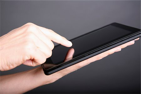 fingers holding - A man using a digital tablet, close-up of hand Stock Photo - Premium Royalty-Free, Code: 653-05976892