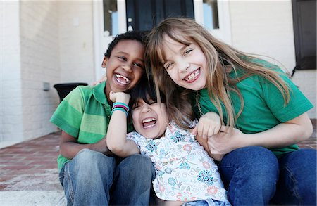 preteen touch - Three kids laughing affectionately while sitting on the front stoop Stock Photo - Premium Royalty-Free, Code: 653-06534071