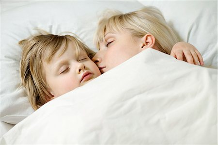 A mother and her young daughter sleeping a bed side by side Stock Photo - Premium Royalty-Free, Code: 653-06534086