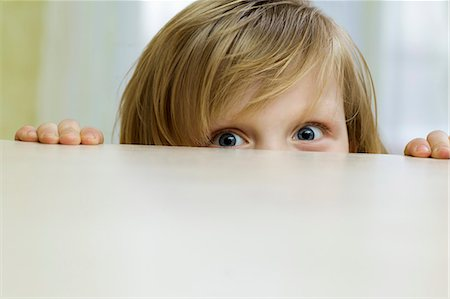 A mischievous girl peeking over the top of a table Stock Photo - Premium Royalty-Free, Code: 653-06534081