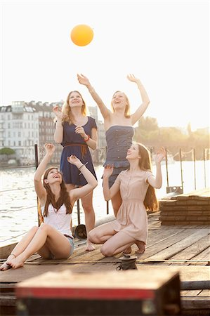 Four female friends tossing a ball around on a jetty next to Spree River, Berlin, Germany Stock Photo - Premium Royalty-Free, Code: 653-06534114