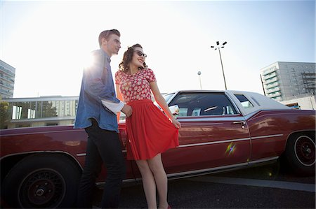 red - A cheerful rockabilly couple standing next to a vintage car Stock Photo - Premium Royalty-Free, Code: 653-06534129