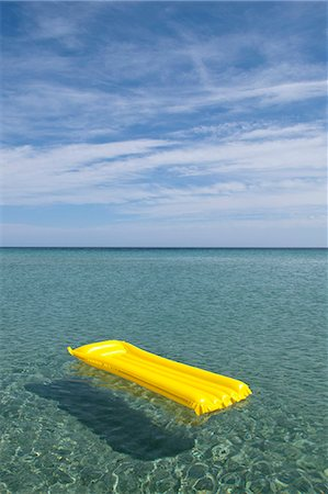 A yellow inflatable raft floating on the sea, Budoni, Sardinia, Italy Stock Photo - Premium Royalty-Free, Code: 653-06534144