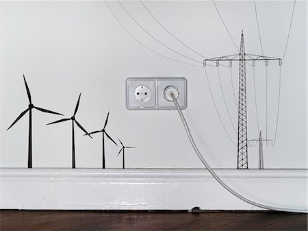 A plug in an outlet in between decals of wind turbines and electricity pylons Stock Photo - Premium Royalty-Free, Code: 653-06534182