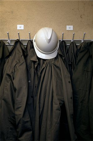 A hard hat and uniforms hanging on hooks Stock Photo - Premium Royalty-Free, Code: 653-06534239