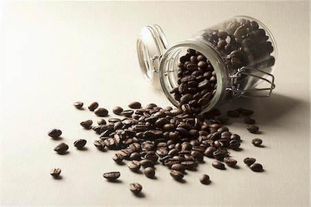 Coffee beans spilling from a jar Stock Photo - Premium Royalty-Free, Code: 653-06534265