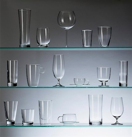A collection of various types of drinking glasses arranged neatly on three shelves Stock Photo - Premium Royalty-Free, Code: 653-06534319
