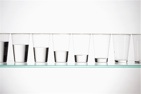 A row of glasses with varying amounts of water descending from full to empty Stock Photo - Premium Royalty-Free, Code: 653-06534322