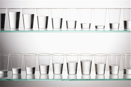 Two shelves with glasses of water filled with varying amounts of water Stock Photo - Premium Royalty-Free, Code: 653-06534330