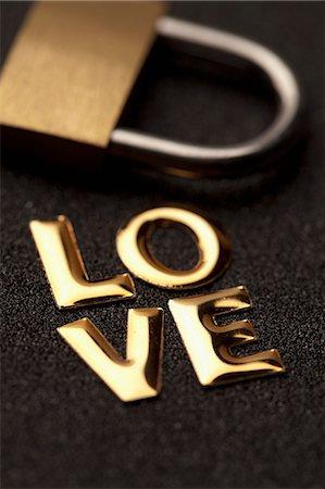 represented - Single word 'love' in gold lettering beside padlock Stock Photo - Premium Royalty-Free, Code: 653-06534357