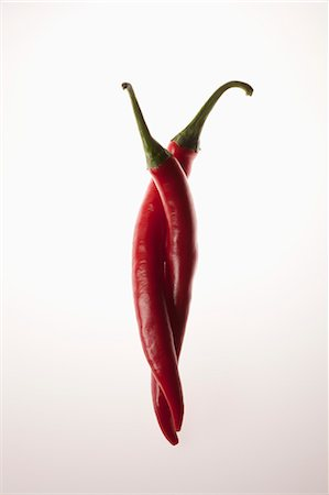 represented - Two red chili peppers intertwined Stock Photo - Premium Royalty-Free, Code: 653-06534371