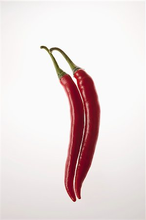 represented - Two red chili peppers touching in a row Stock Photo - Premium Royalty-Free, Code: 653-06534385