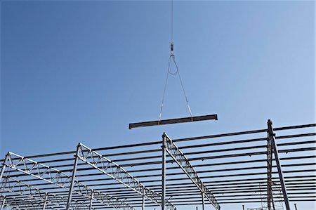Crane lowering steel beam towards construction frame Stock Photo - Premium Royalty-Free, Code: 653-06534488