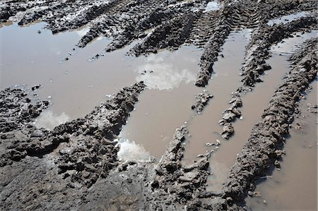 Range of construction vehicle tracks across a puddle on construction site Stock Photo - Premium Royalty-Free, Code: 653-06534483