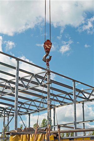 Crane hook with construction site in background Stock Photo - Premium Royalty-Free, Code: 653-06534499