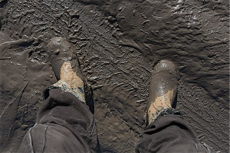 Construction worker's feet in mud of tyre track Stock Photo - Premium Royalty-Free, Code: 653-06534528