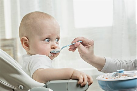 Mother spoon feeding her baby Stock Photo - Premium Royalty-Free, Code: 653-06534598