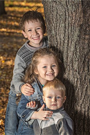 Three cheerful siblings posing next to a tree trunk Stock Photo - Premium Royalty-Free, Code: 653-06534605