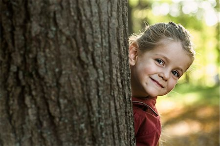 A young smiling girl peeking from behind a tree trunk Stock Photo - Premium Royalty-Free, Code: 653-06534658