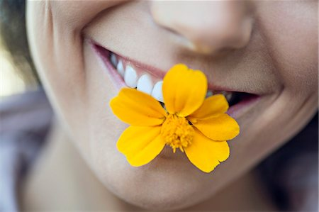 A young grinning woman holding a single flower in her mouth Stock Photo - Premium Royalty-Free, Code: 653-06534702