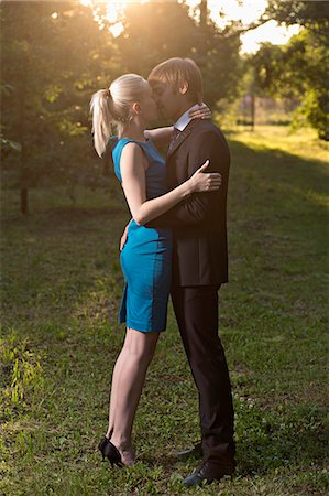 passion - A well-dressed couple embracing and kissing in a park Stock Photo - Premium Royalty-Free, Code: 653-06534733