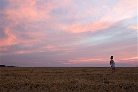 A pregnant woman standing in a remote field under a dramatic sky Stock Photo - Premium Royalty-Free, Code: 653-06534758