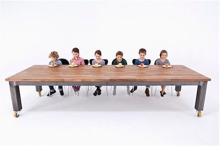 sad child sitting - Six kids looking down at apples on their plates with uncertainty Stock Photo - Premium Royalty-Free, Code: 653-06534820